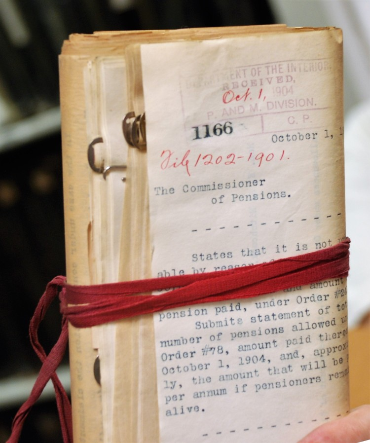 bundle of US pension documents from 1906 bound in red tape